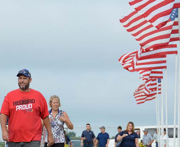 Farm Progress Show attendees walking next to american flags